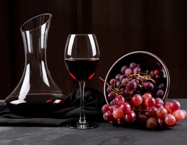 Vista lateral de la jarra con vino tinto y uva en horizontal oscuro