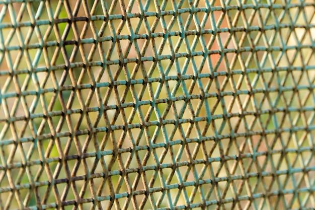 Vista lateral de la jaula oxidada. fondo verde