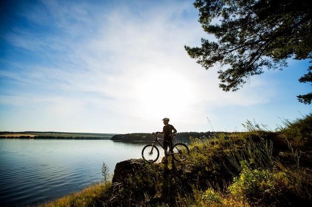 Vista lateral del jinete en una bicicleta de pie sobre una roca y disfrutando del atardecer. motivación e inspiración para la aventura.