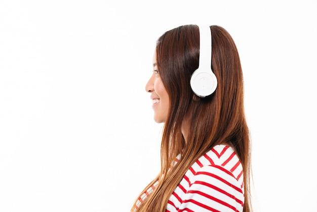 Vista lateral de una joven asiática en auriculares