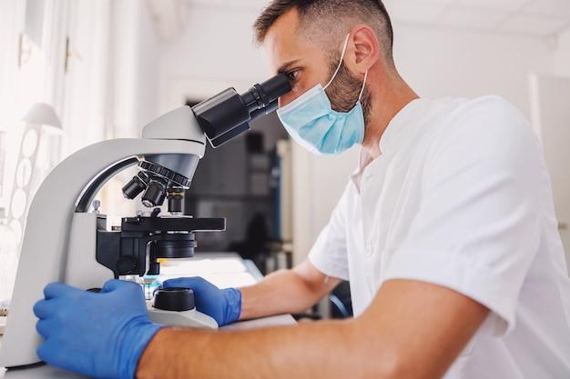Vista lateral del joven asistente de laboratorio masculino dedicado con guantes de goma y mascarilla con microscopio.