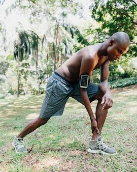 Vista lateral de un joven atleta sin camisa estirando su pierna en el parque