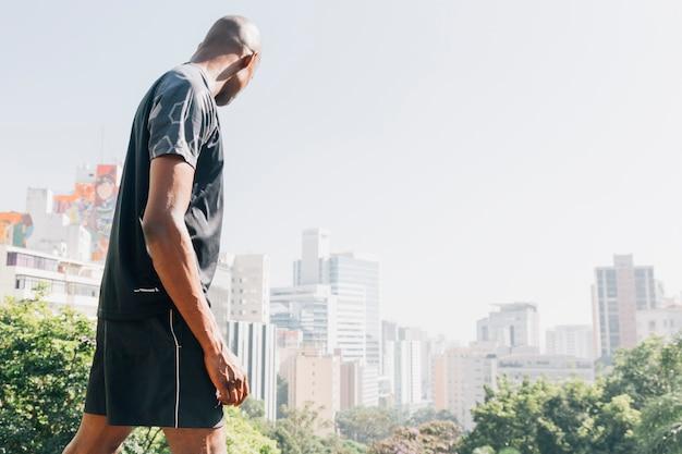 Vista lateral de un joven atleta mirando el horizonte de la ciudad