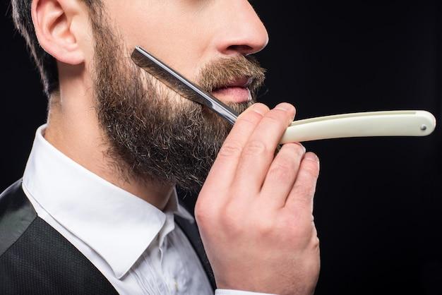 Vista lateral de un joven barbudo brutal con navaja de afeitar recta.