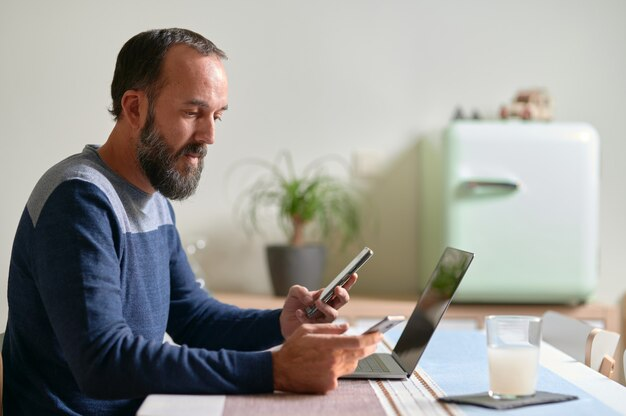 Vista lateral del joven barbudo con un teléfono inteligente en cada mano y su computadora portátil sobre la mesa multitarea, interrupciones de trabajo