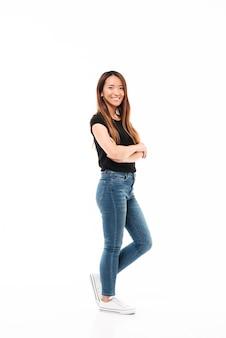 Vista lateral de la joven y bella mujer china en camiseta negra y jeans de pie con las manos cruzadas, mirando a la cámara
