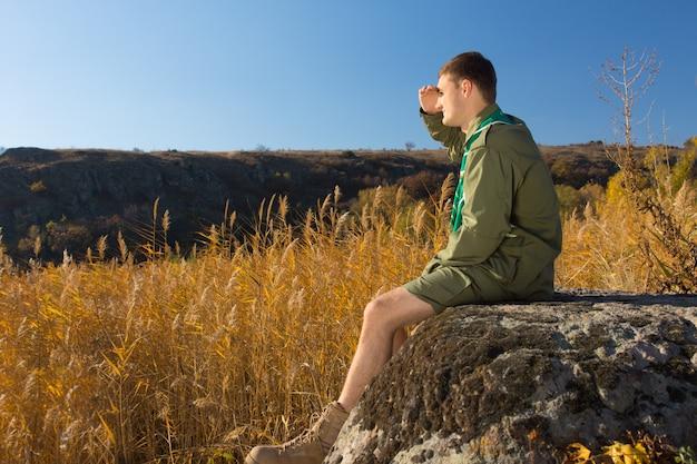 Vista lateral del joven boy scout blanco sentado en old big rock mirando el amplio campo marrón en una temporada de otoño.