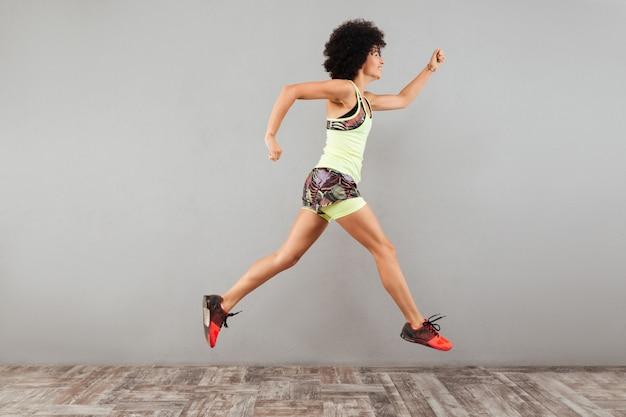 Vista lateral de la joven corriendo
