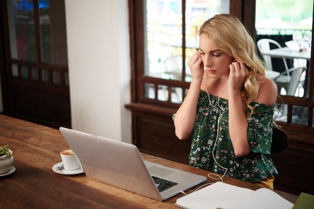 Vista lateral de la joven dama rubia poniéndose los auriculares para escuchar la música en la computadora portátil