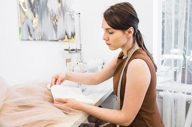 Vista lateral de un joven diseñador femenino que trabaja en la tienda