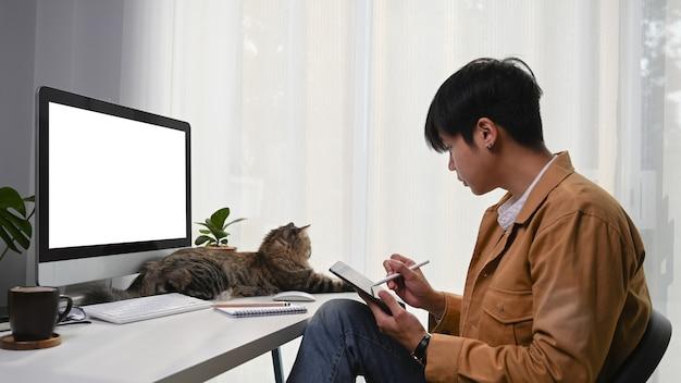 Vista lateral del joven diseñador gráfico que trabaja con tableta digital y lindo gato frente a él.