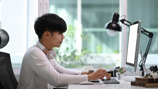 Vista lateral del joven diseñador gráfico sentado en el estudio gráfico frente a la computadora mientras trabaja en línea