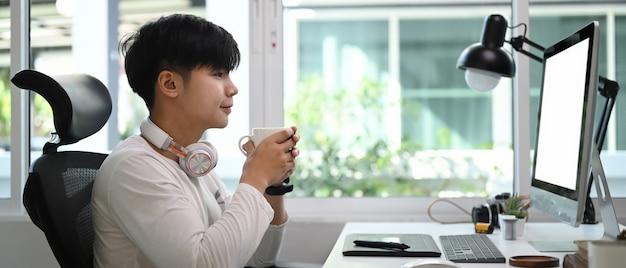 Vista lateral del joven diseñador gráfico sosteniendo una taza de café y sentado frente a su computadora