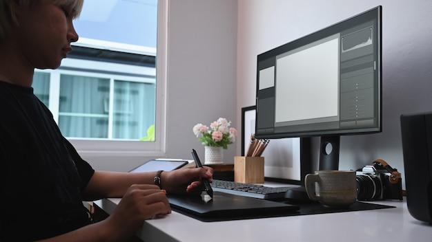 Vista lateral de la joven diseñadora gráfica trabajando con tableta gráfica en la oficina moderna.