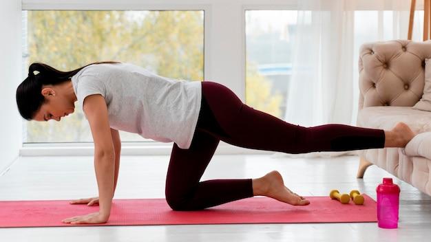 Vista lateral de la joven embarazada haciendo yoga en el interior