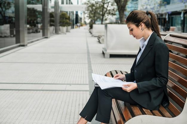 Vista lateral de una joven empresaria sentada en un banco leyendo los documentos en papel