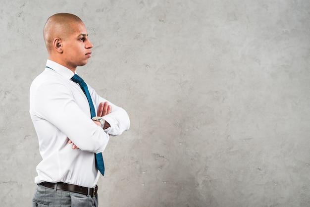 Vista lateral de un joven empresario con los brazos cruzados de pie contra la pared gris