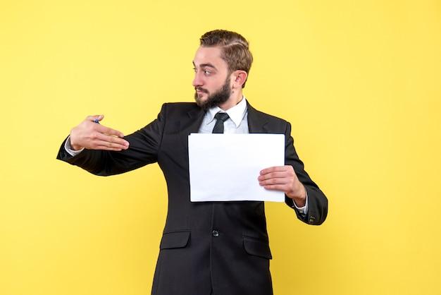 Vista lateral del joven empresario mira a un lado y apunta con la mano derecha a un papel en blanco en la pared amarilla