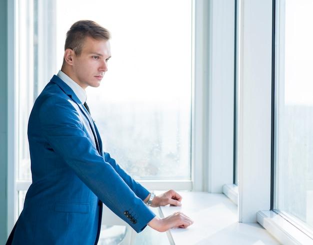 Vista lateral de un joven empresario de pie junto a la ventana en la oficina