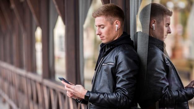 Vista lateral joven escuchando música con auriculares afuera