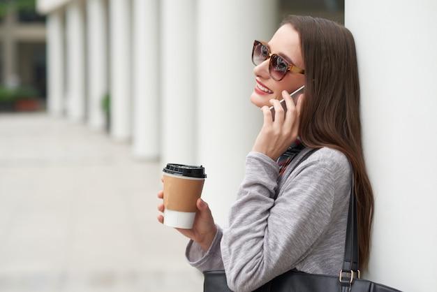 Vista lateral de la joven en gafas de sol haciendo llamada telefónica apoyándose en la pared del edificio