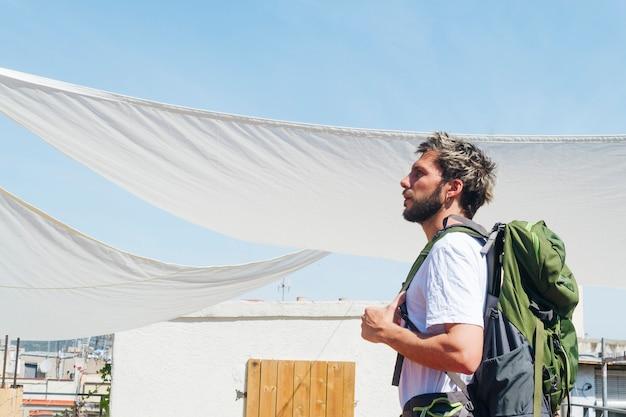 Vista lateral del joven llevando mochila durante el viaje