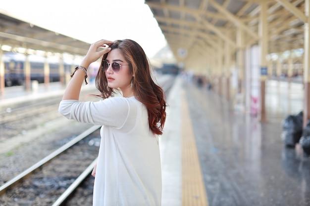 Vista lateral joven mujer asiática de pie y posar en la estación de tren con cara sonriente y belleza