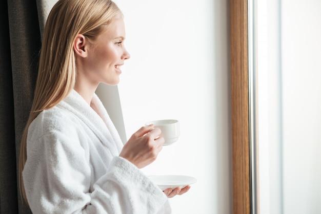 Vista lateral de una joven mujer atractiva en bata de baño