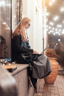 Vista lateral de la joven mujer usando una computadora portátil en la calle con la ciudad de noche