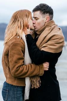 Vista lateral de la joven pareja besándose en invierno al aire libre