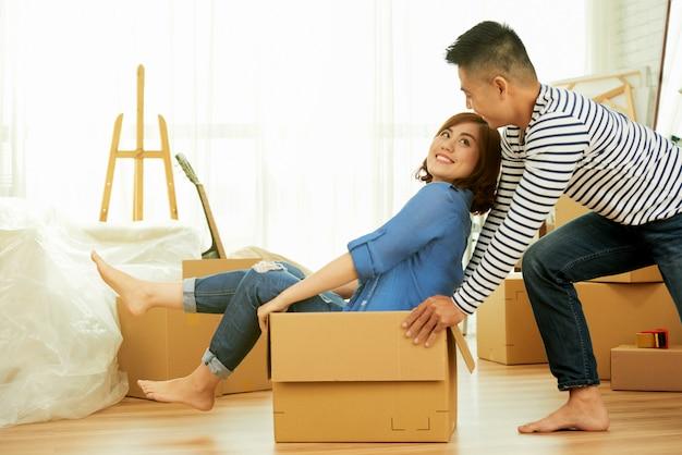 Vista lateral de la joven pareja divirtiéndose con paquete en una habitación