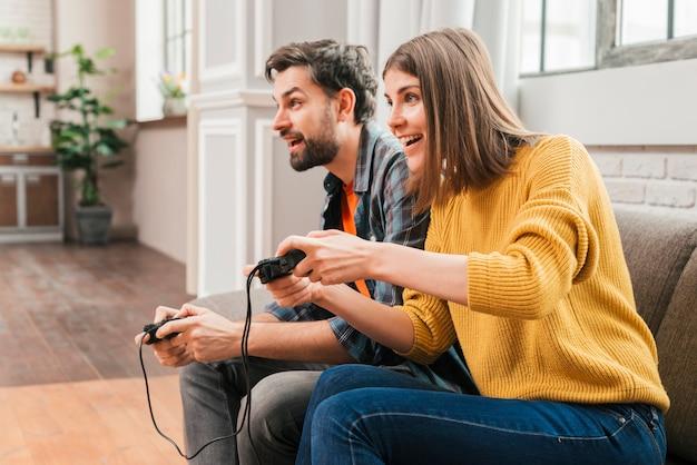 Vista lateral de una joven pareja jugando al videojuego en casa.