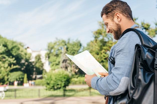 Vista lateral del joven sonriente llevando mochila y leyendo el mapa al aire libre