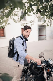Vista lateral de un joven con su moto