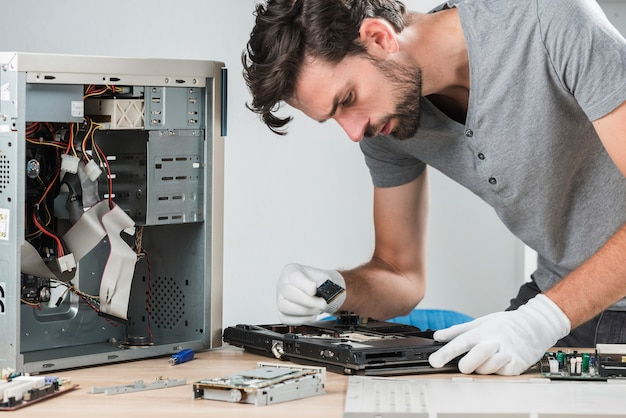 Vista lateral de un joven técnico masculino examinando una computadora portátil ram