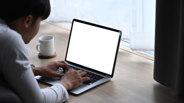 Vista lateral del joven tumbado en un piso de madera y usando una computadora portátil simulada con pantalla blanca.