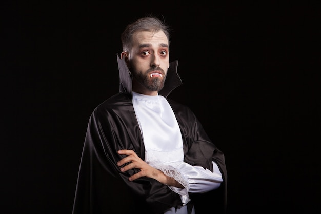 Vista lateral del joven vestido como un vampiro mirando curioso a la cámara. drácula manteniendo los brazos cruzados.