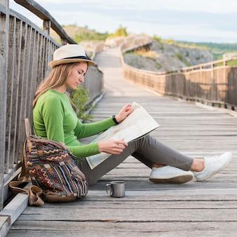 Vista lateral joven viajero revisando el mapa