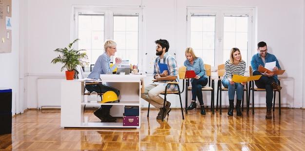 Vista lateral de jóvenes atractivos seguros sentados en línea con carpetas frente al jefe para la entrevista.