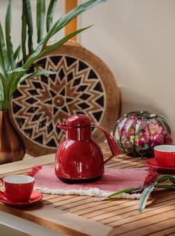 Vista lateral del juego de té rojo de tazas y tetera en una mesa de madera