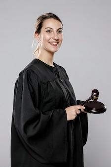 Vista lateral de la jueza sonriente con martillo