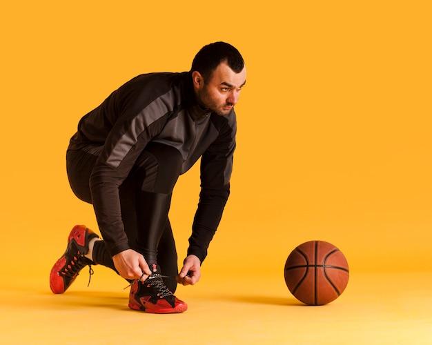 Vista lateral del jugador de baloncesto masculino atar cordones de los zapatos con balón y espacio de copia