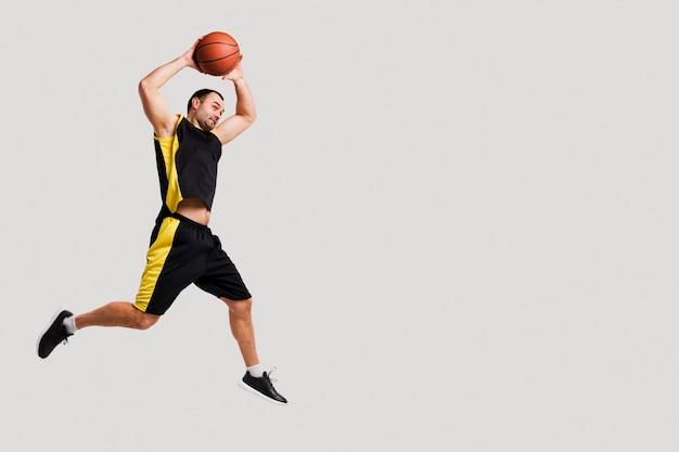 Vista lateral del jugador de baloncesto posando en el aire mientras lanza la pelota con espacio de copia