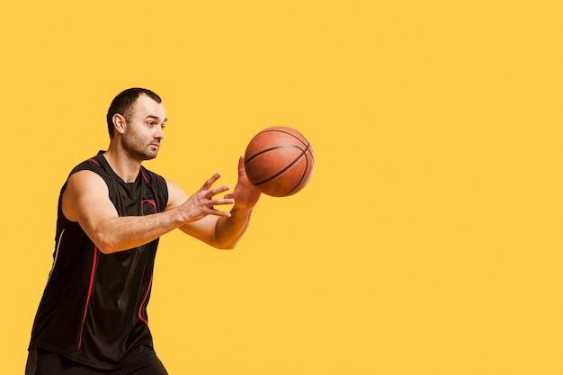 Vista lateral del jugador masculino lanzando baloncesto con espacio de copia