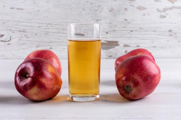 Vista lateral jugo de manzana con manzanas rojas en mesa de madera blanca