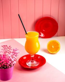 Vista lateral de jugo de naranja fresco en vidrio en rosa