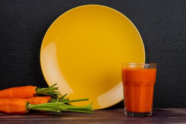 Vista lateral de jugo de zanahoria y zanahorias con plato vacío sobre superficie de madera y fondo negro