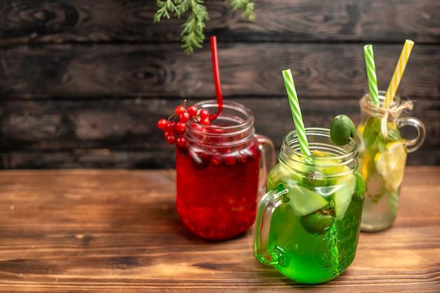 Vista lateral de jugos frescos orgánicos en botellas servidas con tubos y frutas en el lado izquierdo sobre una mesa marrón