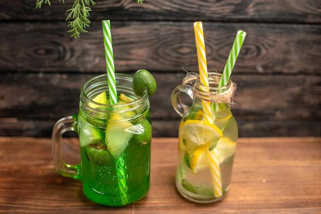 Vista lateral de jugos frescos orgánicos en botellas servidas con tubos y frutas sobre una mesa marrón