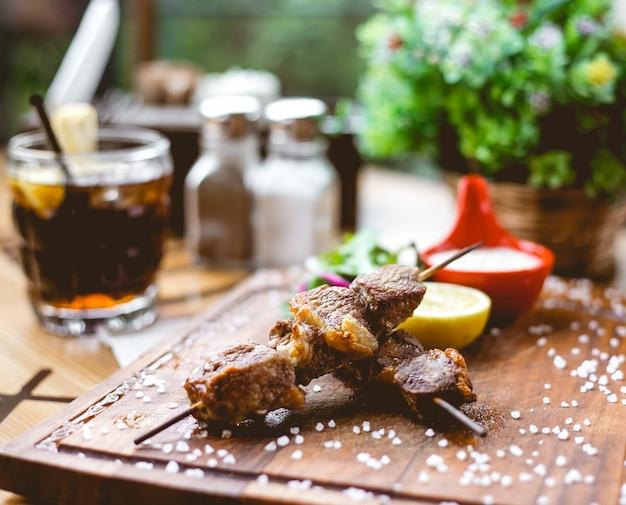 Vista lateral kebab de carne en brochetas con sal y una rodaja de limón en el tablero